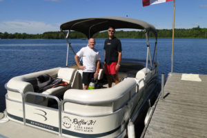 2 People on a pontoon boat getting ready for a cruise of Katchewanooka Lake